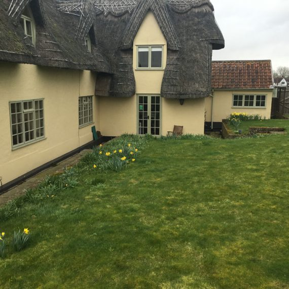 pretty thatched cottage with narrow side path and extensive lawns