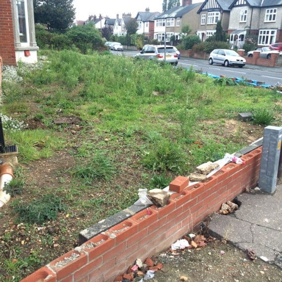 front garden with damaged wall and lots of weeds