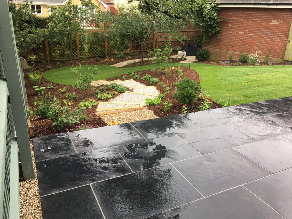 sloping garden with black basalt patio in the foreground and winding path leading through a lawn