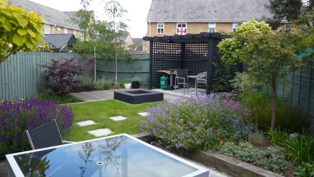 small back garden with cottage garden planting, an arbour and stepping stones through the lawn
