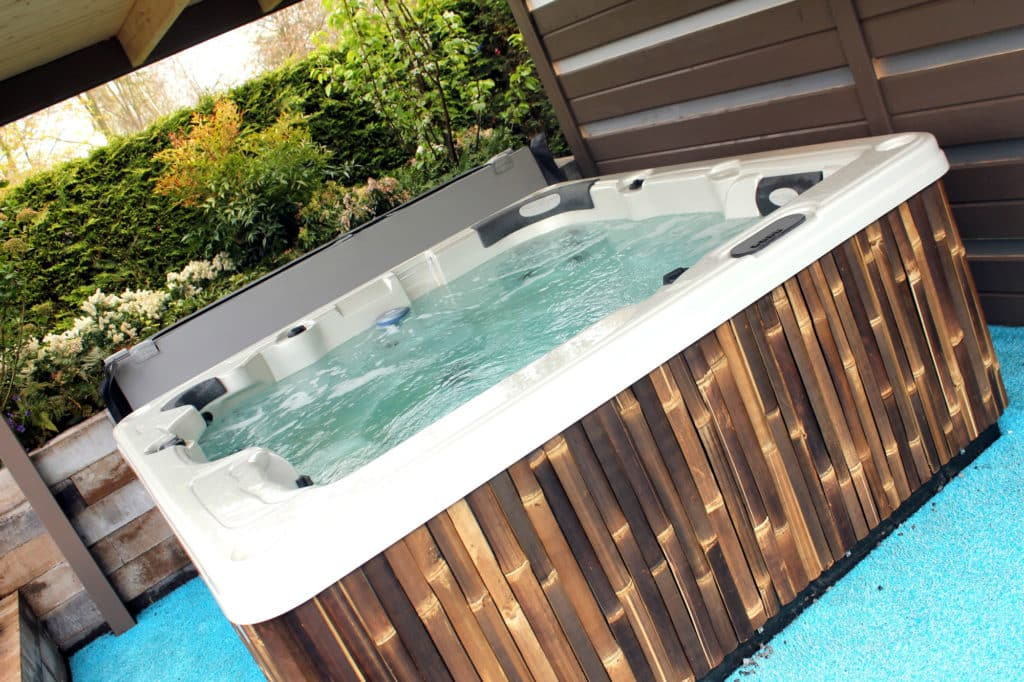 hot tub with landscaping features such as a pergola and planting for privacy