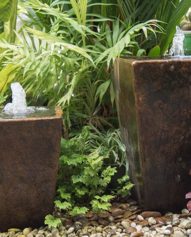 two ceramic planters converted into water features and set amongst beautiful foliage plants