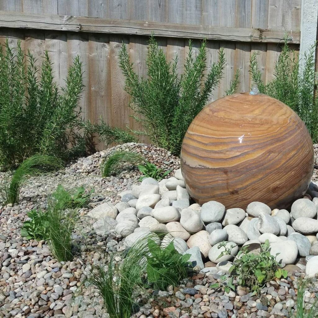 stone globe with pebbles and low maintenance planting