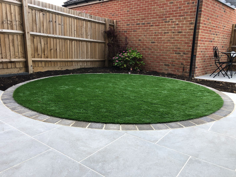 circular artificial grass lawn edged with limestone setts