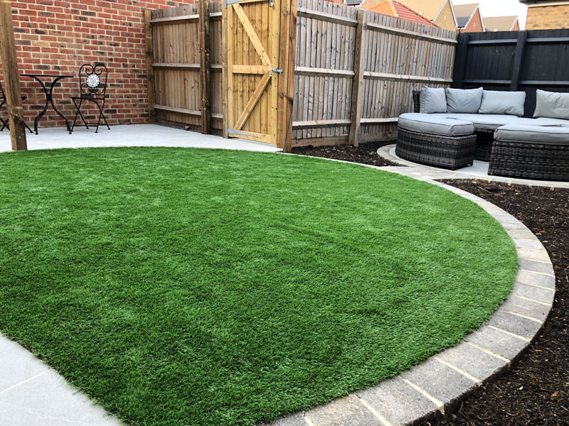 artificial grass lawn with circular seating area in the background
