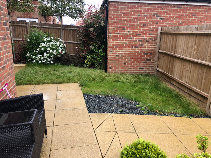 new build back garden with beige paving and worn out lawn