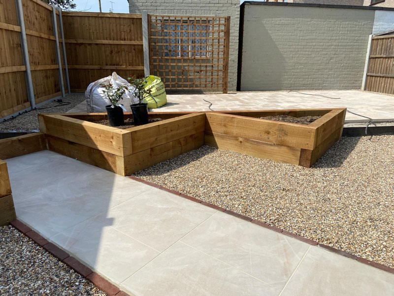 porcelain paver path with triangular shaped raised beds