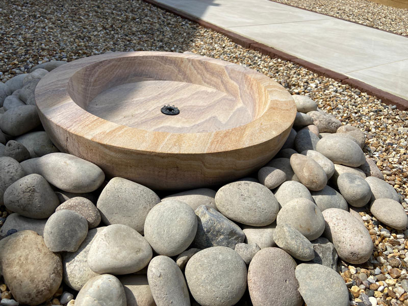 circular stone water feature surrounded by pebbles