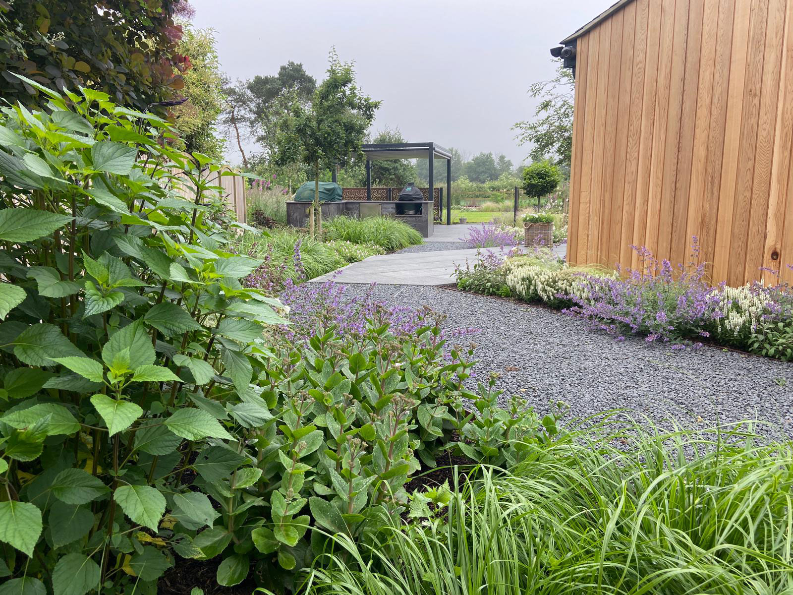 garden path in grey gravel leading to porcelain patio and outdoor kitchen
