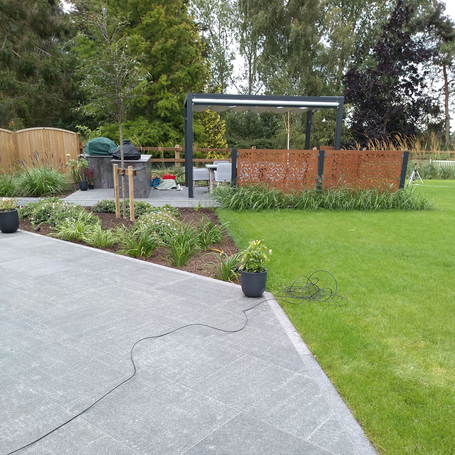 view from patio across lawns to garden pergola with corten screens