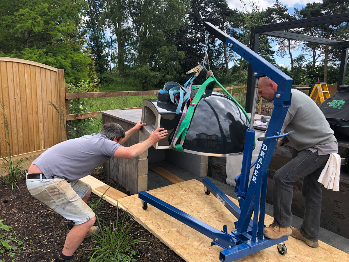 landscapers using lifting gear to install outdoor pizza oven